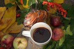 En ljus sammansättning för A med en kopp av starkt svart te, en söt bulle med russin, askabär, äpplen och färgrika höstsidor på Arkivbilder