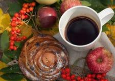 En ljus sammansättning för A med en kopp av starkt svart te, en söt bulle med russin, askabär, äpplen och färgrika höstsidor på Royaltyfri Fotografi