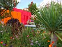 En ljus trädgård med blommor och träd Royaltyfria Bilder