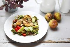 En ljus vegetarisk sallad med fikonträdet, kronärtskocka, gurka, tomater, feta på ruccolasidor som överträffas med hallonsås arkivfoton