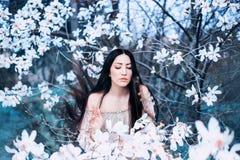 En ljuv ung mörker-haired dam med stängda ögon, ställningar i trädgården av att blomma magnolior hår flyger upp med fotografering för bildbyråer
