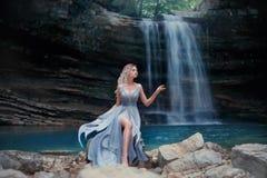 En lockig blond flicka i en lyxig blå klänning sitter på vita stenar mot bakgrunden av ett sagolikt landskap Flod royaltyfria bilder