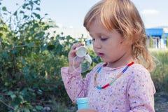 En lockig liten flicka som blåser såpbubblor Fotografering för Bildbyråer