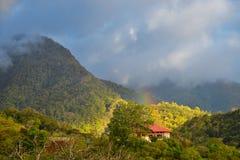 En loge upp höjdpunkt i ett berg med en regnbåge royaltyfri bild