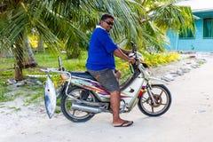 En lokal infödd Polynesian man på en motorcykel med en tonfisk, Tuvalu royaltyfri fotografi