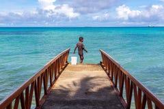 En lokal Polynesian pojke som fiskar från en bryggapir i en tropisk azur turkosblåttlagun, Tuvalu, Oceanien royaltyfri fotografi