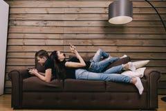 En los adolescentes del amor que mienten en cama con el teléfono celular Imágenes de archivo libres de regalías