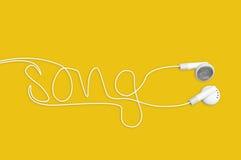 En los auriculares del oído que escriben la canción en amarillo Fotografía de archivo libre de regalías