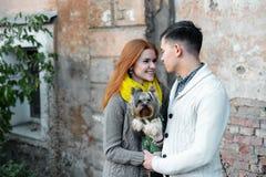 En los pares del amor que abrazan con las flores en el parque Fotografía de archivo libre de regalías