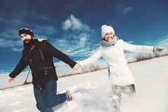 En los pares del amor que corren en campo nevoso Fotos de archivo