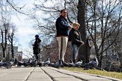 En los primeros días calientes de parque de la ciudad de la primavera la gente desconocida alimentó pájaros Imágenes de archivo libres de regalías
