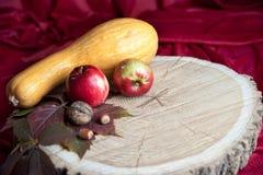 En los registros de madera redondos son una calabaza, dos manzanas, nueces y haz Foto de archivo
