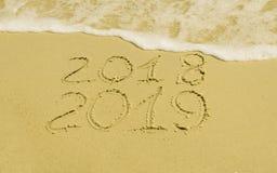 En los símbolos de oro 2018 de la arena 2019, lavados la agua de mar Imagen de archivo libre de regalías