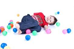 En älskvärd unge leker med bollar Royaltyfri Foto