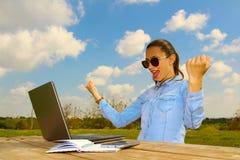 En lyckad funktionsduglig kvinna med en bärbar dator royaltyfri bild