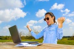 En lyckad funktionsduglig kvinna med en bärbar dator och armar upp Fotografering för Bildbyråer