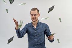 En lyckad ung man i skjortan och exponeringsglas som rymmer upp en bunt av kassa och kast det runt om dig arkivfoto