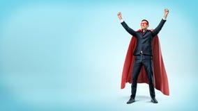 En lycklig affärsman i ett rött uddeanseende för superhero i seger poserar på blå bakgrund royaltyfria foton