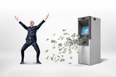 En lycklig affärsman står på en vit bakgrund nära en ATM-maskin med många dollarsedlar som omkring flyger royaltyfria foton