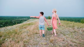 En lycklig barndom - en flicka och en pojke bär korgar med bär, meddelar, gestikulerar lager videofilmer