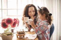 En lycklig familj har frukosten hemma vid fönstret på tabellen Blommor och kaffe Mom och dotter kopiera avstånd royaltyfri bild