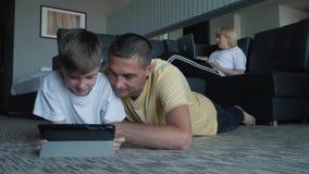 En lycklig familj med ett barn som ligger på mattan och använder en digital minnestavla och smartphones Moderna teknologier av lager videofilmer