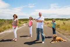 En lycklig familj på en tyst landsväg Arkivfoto