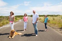 En lycklig familj på en tyst landsväg Arkivbild