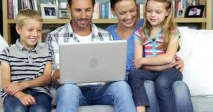 En lycklig familj som tycker om ett ögonblick med en dator stock video