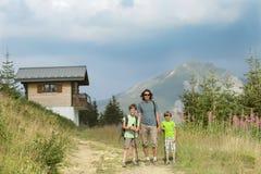 En lycklig familjfader och två pojkar går i berg royaltyfria foton