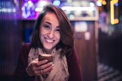En lycklig flicka använda din mobiltelefon i en stång fotografering för bildbyråer