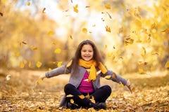 En lycklig flicka går i höstskogen arkivfoton