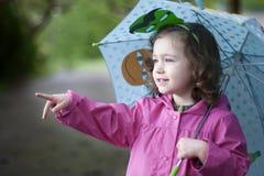 En lycklig flicka med ett färgrikt paraply royaltyfri foto
