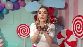 En lycklig flicka med slag för blont hår på ett glitter eller en konfetti långsam rörelse stock video