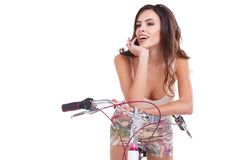 En lycklig flicka, sitter på en cykel, hållhanden nära framsidan och skratt bakgrund isolerad white royaltyfri foto
