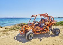 En lycklig flicka som kör en barnvagn på en stranddyn sätta på land paraplyer för orangen för kos för kefalos för den stolsgreece royaltyfria foton