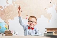 En lycklig glad skolpojke bär exponeringsglas, sitter på ett skrivbord och lyftte hans hand uppåt Royaltyfri Foto