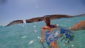 En lycklig grabb simmar in i havet och tar bilder av honom på iPhonen stock video
