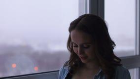 En lycklig gravid kvinna står på ett stort panorama- fönster som lokaliseras på en hög höjd Han trycker på hans mage med hans
