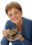 En lycklig hög kvinna som dricker en kupa av kaffe Arkivfoto