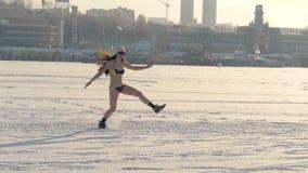 En lycklig kvinna i en baddräkt hoppar över snö lager videofilmer