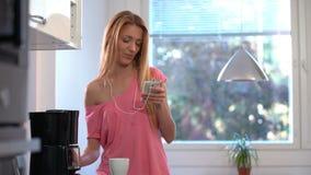 En lycklig kvinna i pyjamas som dansar i köket, kaffe, hörlurar, smartphone stock video