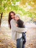 En lycklig kvinna rymmer på armar som omfamnar hennes lilla son arkivfoton