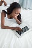 En lycklig kvinna som ligger på henne buk genom att använda en anteckningsbok Royaltyfria Bilder