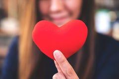 En lycklig kvinna som rymmer ett rött hjärtatecken med mening förälskat arkivbild