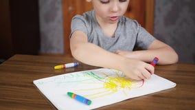 En lycklig le förskolebarnpojke sitter på en tabell och attraktioner med ljusa blyertspennor på papper Utveckling och utbildning  stock video