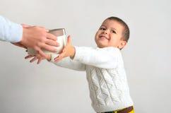 En lycklig le pojke mottar en gåva från händerna av parenen Arkivbilder
