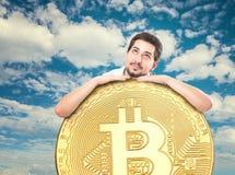 En lycklig man med ett enormt bitcoinmynt på en härlig himmel royaltyfri foto