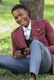 En lycklig mansvartarbetare som ser hans telefon royaltyfri bild