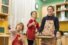 En lycklig moder med tre barn gjorde ljust rödbrun kex Gladlynta tre och lyckliga barn pojken är 3 gamla år och giren två Fotografering för Bildbyråer